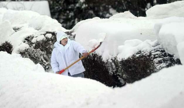 Ana Farias clears the sidewalk near her home on Cottage Street in Danbury late Wednesday morning, January 12, 2011. Photo: Carol Kaliff / The News-Times
