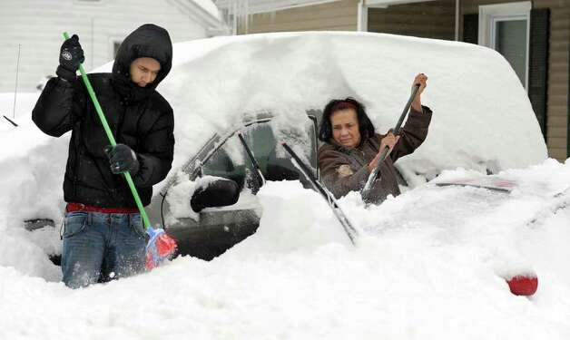 Ariel Suero, left and his grandmother Belais Reyes, dig their cars out from the snow Wednesday, January 12, 2011. Photo: Carol Kaliff / The News-Times
