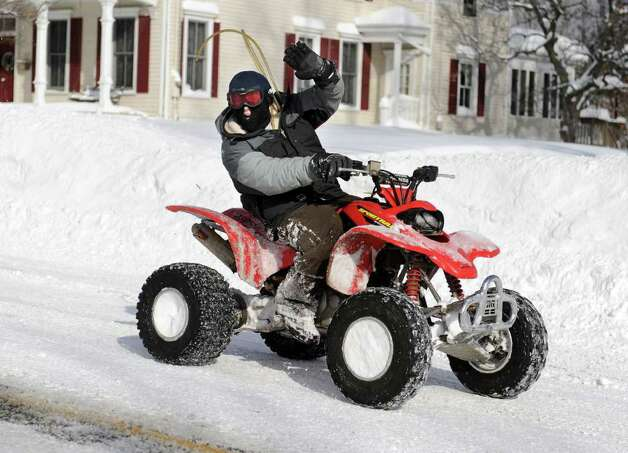 An ATV rider gives a wave as he travels down Main Street in Newtown Wednesday, January 12, 2011. Photo: Carol Kaliff / The News-Times