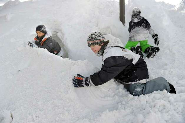 Andrew Almeida, 11, left, of Brookfield, Domenic Cartelli, 11, center and Walter McLean, 12, of Newtown build a tunnel fort in a huge pile of snow at the Big Y shopping center in Newtown, Wednesday, January 12, 2011. Photo: Carol Kaliff / The News-Times