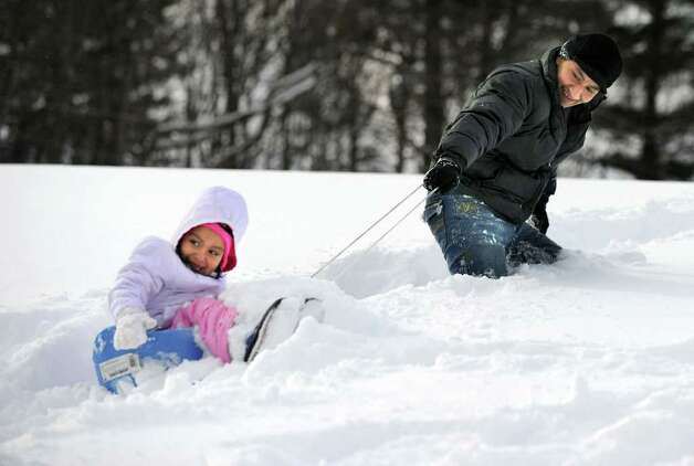 Moses Lima of Danbury pulls his daughter Nicole, 4, up the hill in the deep snow Wednesday. The two were sledding riding at Immaculate High School. Photo taken Wednesday, January 12, 2011. Photo: Carol Kaliff / The News-Times