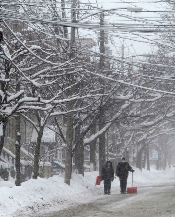 Shovelers walk along snow covered lower Union Street in Schenectady January 12, 2011.  (Skip Dickstein / Times Union) Photo: SKIP DICKSTEIN