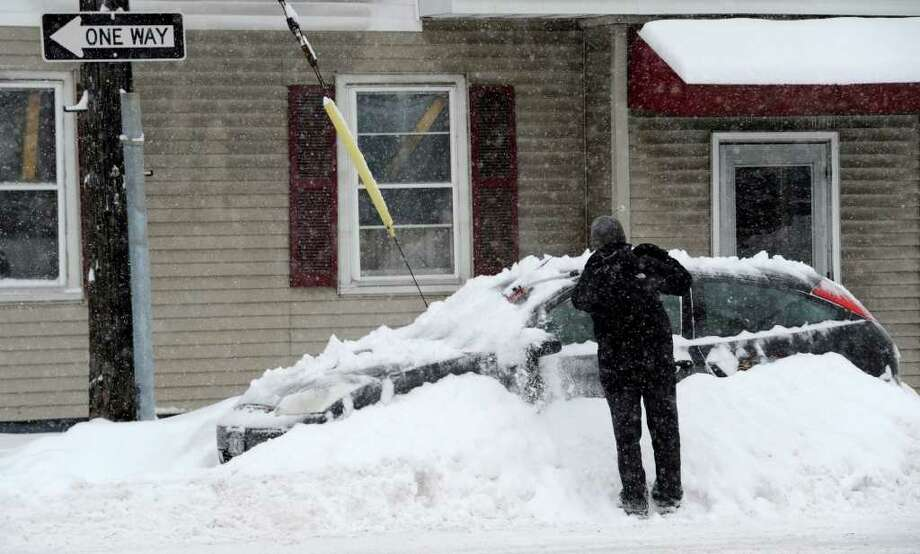 Mathew Williams brushes snow from his car that was plowed in on Fuller Street in Schenectady January 12, 2011.  (Skip Dickstein / Times Union) Photo: SKIP DICKSTEIN