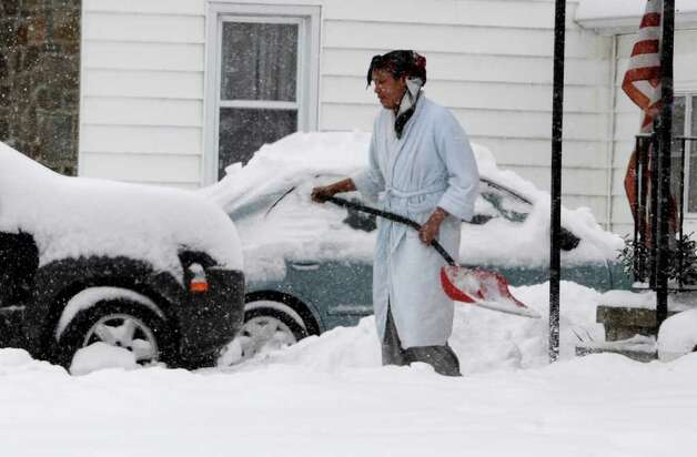 A women walks from her home shovel in hand on Bradley Boulevard  in Schenectady January 12, 2011.  (Skip Dickstein / Times Union) Photo: SKIP DICKSTEIN