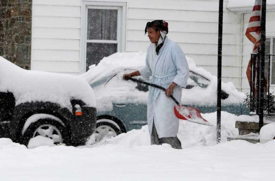 A women walks from her home shovel in hand on Bradley Boulevard  in Schenectady January 12, 2011.  (Skip Dickstein / Times Union) Photo: SKIP DICKSTEIN