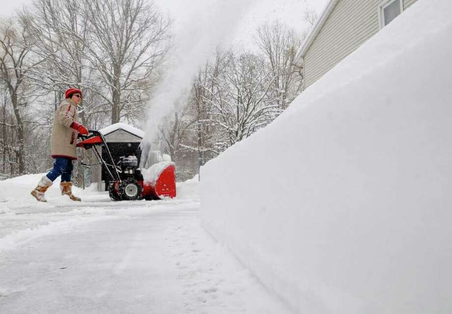 A clean cut is left along the side of the driveway of Gilda Fake as she uses her snowblower in East Greenbush, NY on Wednesday, Jan. 12, 2011.  (Paul Buckowski / Times Union) Photo: Paul Buckowski / 10011727A