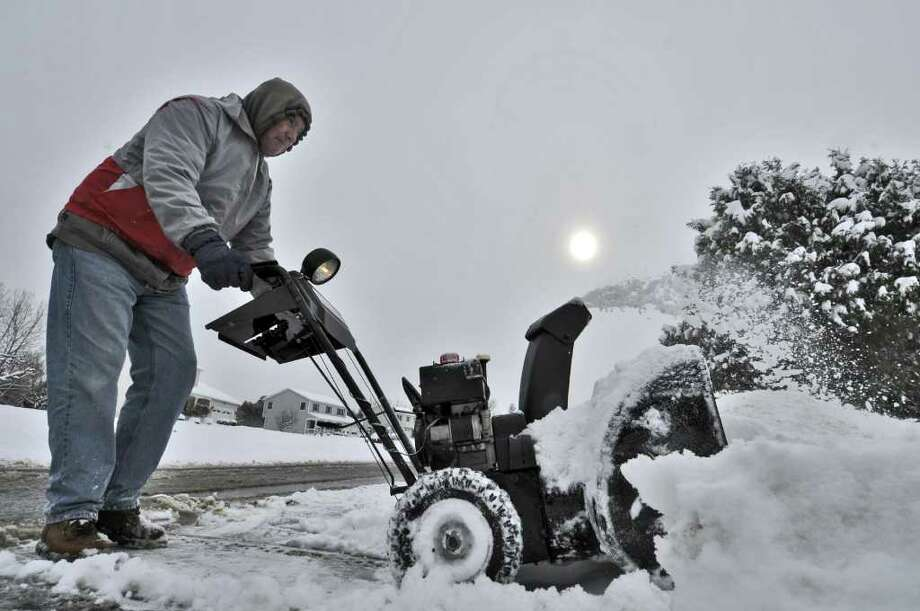 Jim Lyons uses a snowblower to clear the driveway of his Clifton Park, NY home during a snowstorm on Wednesday January 12, 2011.  ( Philip Kamrass / Times Union ) Photo: Philip Kamrass