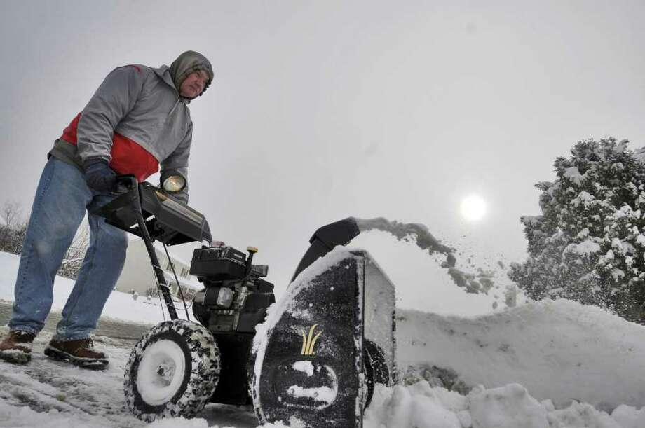 Jim Lyons uses a snowblower to clear the driveway of his Clifton Park, NY home during a snowstorm on Wednesday.  ( Philip Kamrass / Times Union ) Photo: Philip Kamrass
