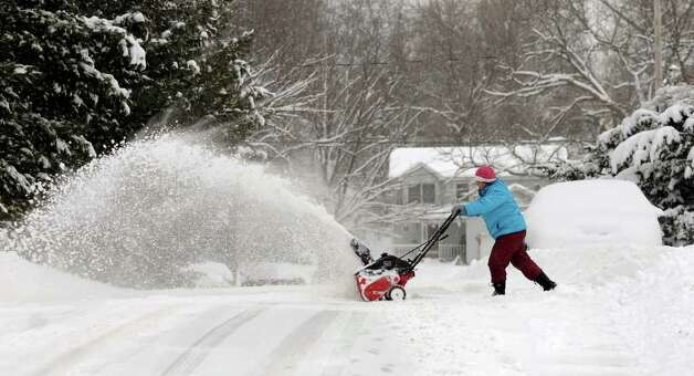 "Phyllis Lounello  clears her driveway of snow during a storm on Wednesday, Jan. 12, 2011, at her home in Albany. Lounello, a lifelong Albany resident, said of the snow, ""I used to play in it, and now I move it. It's not so fun anymore."" (Cindy Schultz / Times Union) Photo: Cindy Schultz"