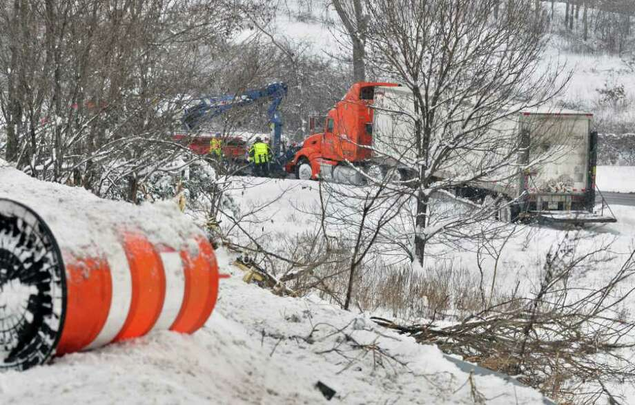 A wrecker winches out a tractor trailer that apparently slid down from the Northway on ramp from Thruway exit 24 onto the I90 eastbound on ramp in Albany Wednesday afternoon January 12, 2011.   (John Carl D'Annibale / Times Union) Photo: John Carl D'Annibale / 10011727A