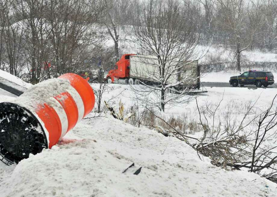 A wrecker winches a tractor trailer at the Northway ramp from the state Thruway on Wednesday in Albany. At 10:30 a.m. the truck driver tried unsuccessfully to head from Exit 24 of the state Thruway up the snow-covered northbound ramp onto the Northway.  The East Penn Manufacuturing truck, fully laden with car batteries, slid down an embankment, taking out over 30 feet of guiderail and dumping 150 gallons of diesel fuel into the median between the ramp and I-90.  The fuel spilled from the damaged saddle fuel tanks, but the truck managed to stay upright. Driver Steven Yenik, 38, of Whitehall, Pa., was ticketed on a charge of imprudent speed by Trooper Jason Meyer. The state Department of Environmental Conservation supervised cleanup, done by Clean Harbor.  (John Carl D'Annibale / Times Union) Photo: John Carl D'Annibale / 10011727A