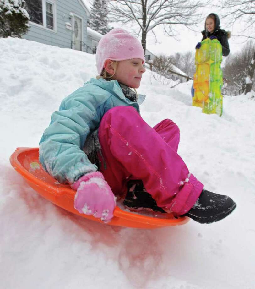 Lily Rogers, age 8 of Guilderland, slides down her front yard hill as Emma Pearson, age 15 of Guilderland, watches in Guilderland, NY on January 12, 2011. (Lori Van Buren / Times Union) Photo: Lori Van Buren