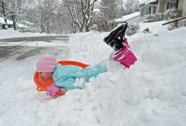 Lily Rogers, age 8 of Guilderland, uses a snow bank in front of her house to sled down in Guilderland, NY on January 12, 2011. (Lori Van Buren / Times Union) Photo: Lori Van Buren