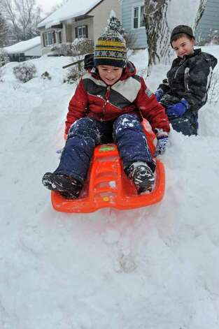 From left, Sammy Pearson, age 7, and Sean Rogers, age 6, slide down a snow bank in front of their home in Guilderland, NY on January 12, 2011. (Lori Van Buren / Times Union) Photo: Lori Van Buren