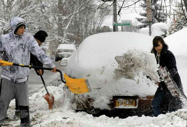 HVVC student Dani Dawes,right, is helped in shoveling her car out by Troy High School students,who had a snow day off, Danny Monk,far left,and Sean Breland on Pawling Avenue in Troy Wednesday afternoon Jan. 12, 2011.( Michael P. Farrell/Times Union ) Photo: Michael P. Farrell