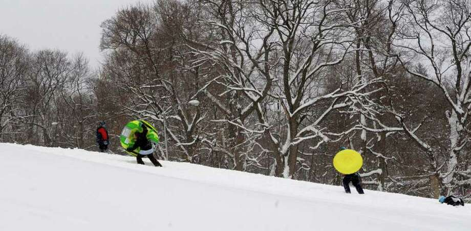 Sledders make their way back up a hill for another slide down at Prospect Park in Troy, NY on Wednesday, Jan. 12, 2011.  (Paul Buckowski / Times Union) Photo: Paul Buckowski / 10011727A