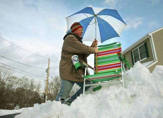 "Marty Casey plants a beach chair and umbrella atop a snow pile outside his Amber Lane home in Milford on Wednesday, January 12, 2011. Casey, a native of Chicago, said he put the items there because to him the storm was just "" a day at the beach"". Photo: Brian A. Pounds / Connecticut Post"