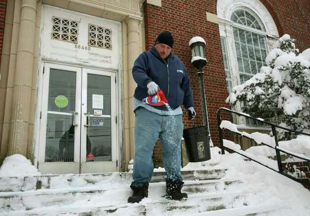 Postal employee Richard Kern salts the steps in front of the Main Post Office in downtown Milford on Wednesday, January 12, 2011. Kern said he began clearing the sidewalk in front of the building at 5 AM. Photo: Brian A. Pounds / Connecticut Post