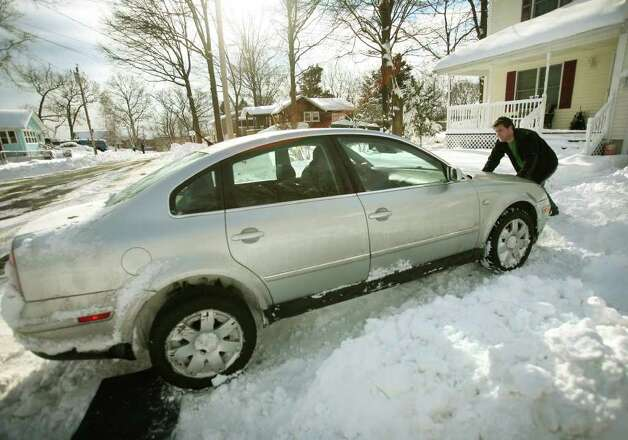 Chris Casey gives his friend Robert Karpel a push after Karpel's car became stuck exiting his friend's driveway on Clayton Street in Milford on Wednesday, January 12, 2011. Photo: Brian A. Pounds / Connecticut Post