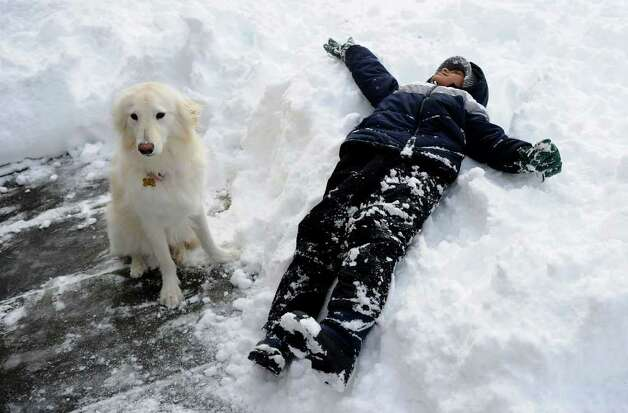 Bryson Davis, 6, and puppy Lacey relax in the snow in Norwalk on Wednesday, January 12, 2011. Photo: Lindsay Niegelberg / Connecticut Post