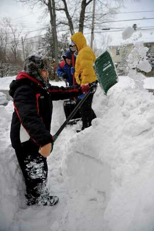 Front to back, Michael Quevedo, 14, Gavin Duff, 13, and Tommy Daly, 13, build a fort on Soundview Avenue in Norwalk on Wednesday, January 12, 2011. Photo: Lindsay Niegelberg / Connecticut Post