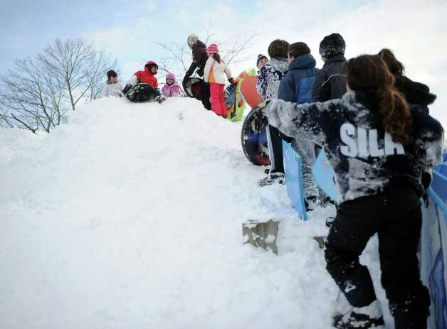 A line forms to sled from the highest point behind Greensfarms Elementary School in Westport on Wednesday, January 12, 2011. The mound of snow was created by plows in the school parking lot. Photo: Lindsay Niegelberg / Connecticut Post