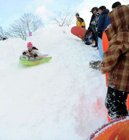 Stephanie Greene, 10, sleds off a giant mound of snow created by plows in the parking lot behind Greensfarms Elementary School in Westport on Wednesday, January 12, 2011. Photo: Lindsay Niegelberg / Connecticut Post