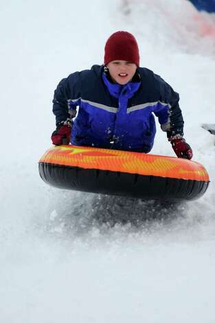 Dobson Cooper, 10, gets some air as he sleds off a giant mound of snow created by plows in the parking lot behind Greensfarms Elementary School in Westport on Wednesday, January 12, 2011. Photo: Lindsay Niegelberg / Connecticut Post