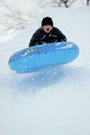 Christopher Puchala, 11, catches some air as he sleds off a giant mound of snow created by plows in the parking lot behind Greensfarms Elementary School in Westport on Wednesday, January 12, 2011. Photo: Lindsay Niegelberg / Connecticut Post