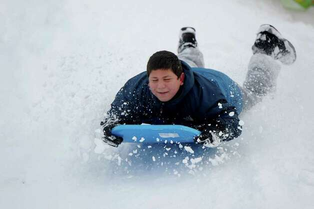 Jack Sila, 12, sleds off a giant mound of snow created by plows in the parking lot behind Greensfarms Elementary School in Westport on Wednesday, January 12, 2011. Photo: Lindsay Niegelberg / Connecticut Post