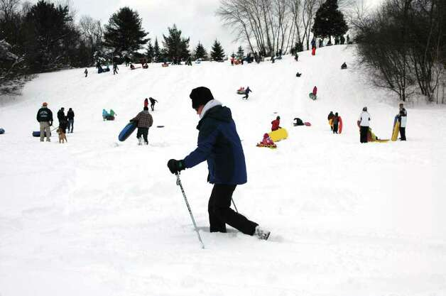 Nikki Rhodes snowshoes across Sturgess Park field while numerous sledders take to the hill in Fairfield Conn. on Wednesday, Jan 12, 2011. Photo: Cathy Zuraw / Connecticut Post