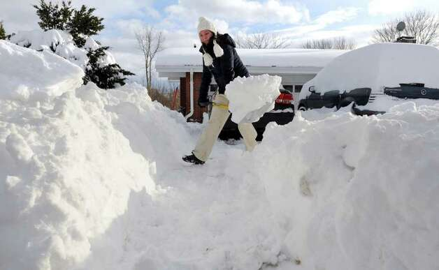 Karolina Alberski shovels a small mountain of snow in her driveway at her home along Ridge Road in Derby, Conn. on Wednesday January 12, 2011. Alberski soon received help from neighbor Phil Soderberg, who used his snowblower to clear the driveway. Photo: Christian Abraham / Connecticut Post