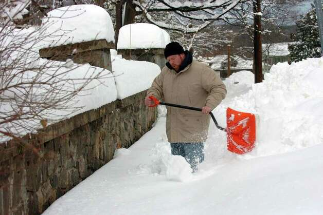 Jay Benanto slowly shovels his way through a long sidewalk in front of his home along Atwater Avenue in Derby, Conn. on Wednesday January 12, 2011. Photo: Christian Abraham / Connecticut Post