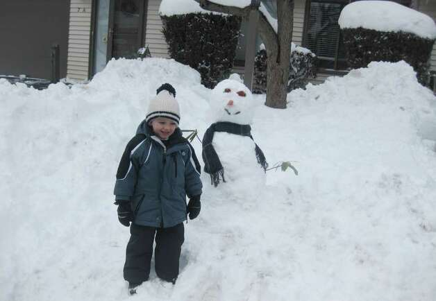 Kenan Healy, 4, of Stamford and a snowman during Wednesday's snowstorm. Contributed photo/Ed Healy Photo: Contributed Photo / Stamford Advocate Contributed