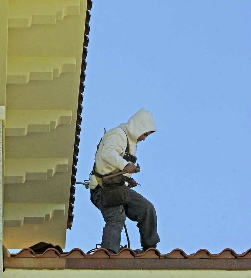 Despite the freezing temperatures when he showed up at work Tuesday morning, Bisente Vargas, an employee with H.B. Neild and Sons Construction, climbed up to the roof of the new Pastoral Center  for the Roman Catholic Diocese of Beaumont to continue laying the clay roof tiles. Dave Ryan/The Enterprise / Beaumont