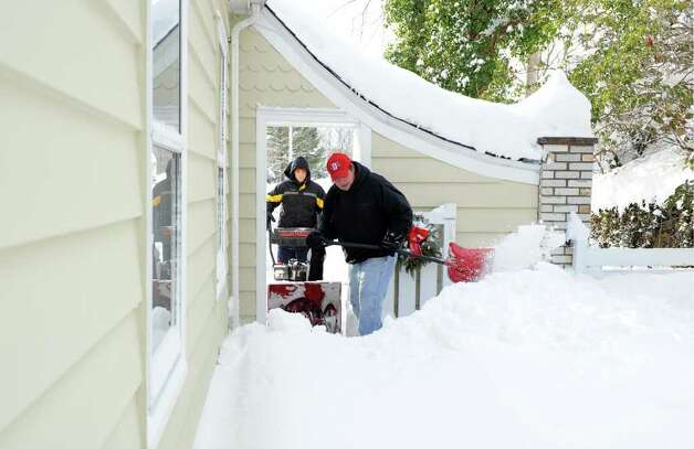 Aftermath and cleanup around Derby, Conn. from a big snowstorm that hit all of New England overnight on Wednesday January 12, 2011. Scott Bottino and his stepson Nick Lemire, in back, shovel and snowblow the walkway at the home of Lynn Wade along Sentinel Hill Road in Derby. Photo: Christian Abraham / Connecticut Post