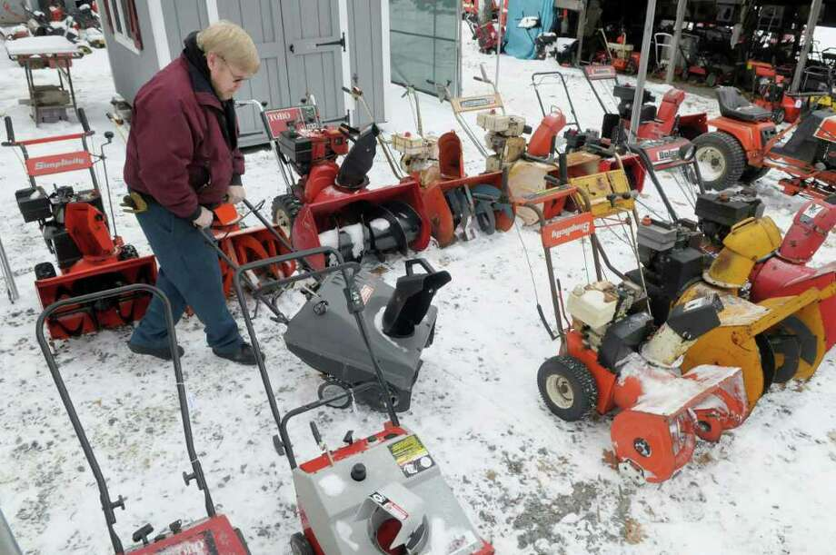 Peter Ostrander, who handles customer service for Tinkers' Premium Power on Route 20 in Schodack, lines up some of the used snowblowers the shop has for sale on Tuesday, Jan. 11, 2011.  The shop is busy getting repaired snowblowers out the door and back to customers and selling their line of new and their assortment of used blowers before the winter storm hits.   (Paul Buckowski / Times Union) Photo: Paul Buckowski / 10011715A
