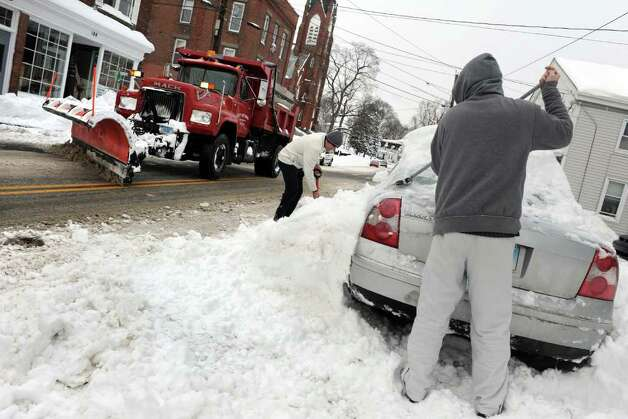 Aftermath and cleanup around Derby, Conn. from a big snowstorm that hit all of New England overnight on Wednesday January 12, 2011. Aaron Ndoj sweeps away snow as he helps his father Gino, in back, along Elizabeth Street in Derby. Photo: Christian Abraham / Connecticut Post