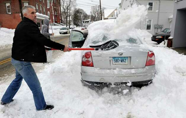 Aftermath and cleanup around Derby, Conn. from a big snowstorm that hit all of New England overnight on Wednesday January 12, 2011. Frank Ndoj shovels away snow as he helps his brother Gino, along Elizabeth Street in Derby. Photo: Christian Abraham / Connecticut Post