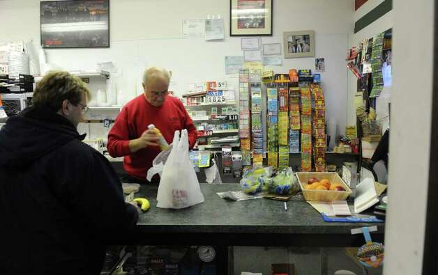 Aftermath and cleanup around Derby, Conn. from a big snowstorm that hit all of New England overnight on Wednesday January 12, 2011. Russell Altimari, who owns and operates Altimari's with his wife Prassede on Elizabeth Street in Derby, bags a customer's items. For the most part, the snowstorm has kept folks away. Photo: Christian Abraham / Connecticut Post