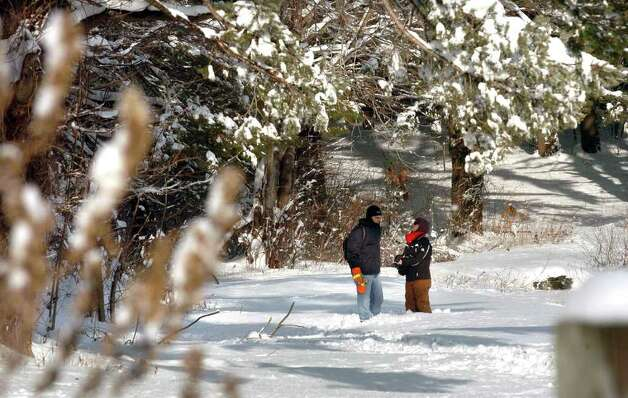 Aftermath and cleanup around Derby, Conn. from a big snowstorm that hit all of New England overnight on Wednesday January 12, 2011. Allan Craddock and his girlfriend Parsons, both of Derby, spend some time exploring and walking in Frank P. Witek Memorial Park in Derby. Photo: Christian Abraham / Connecticut Post