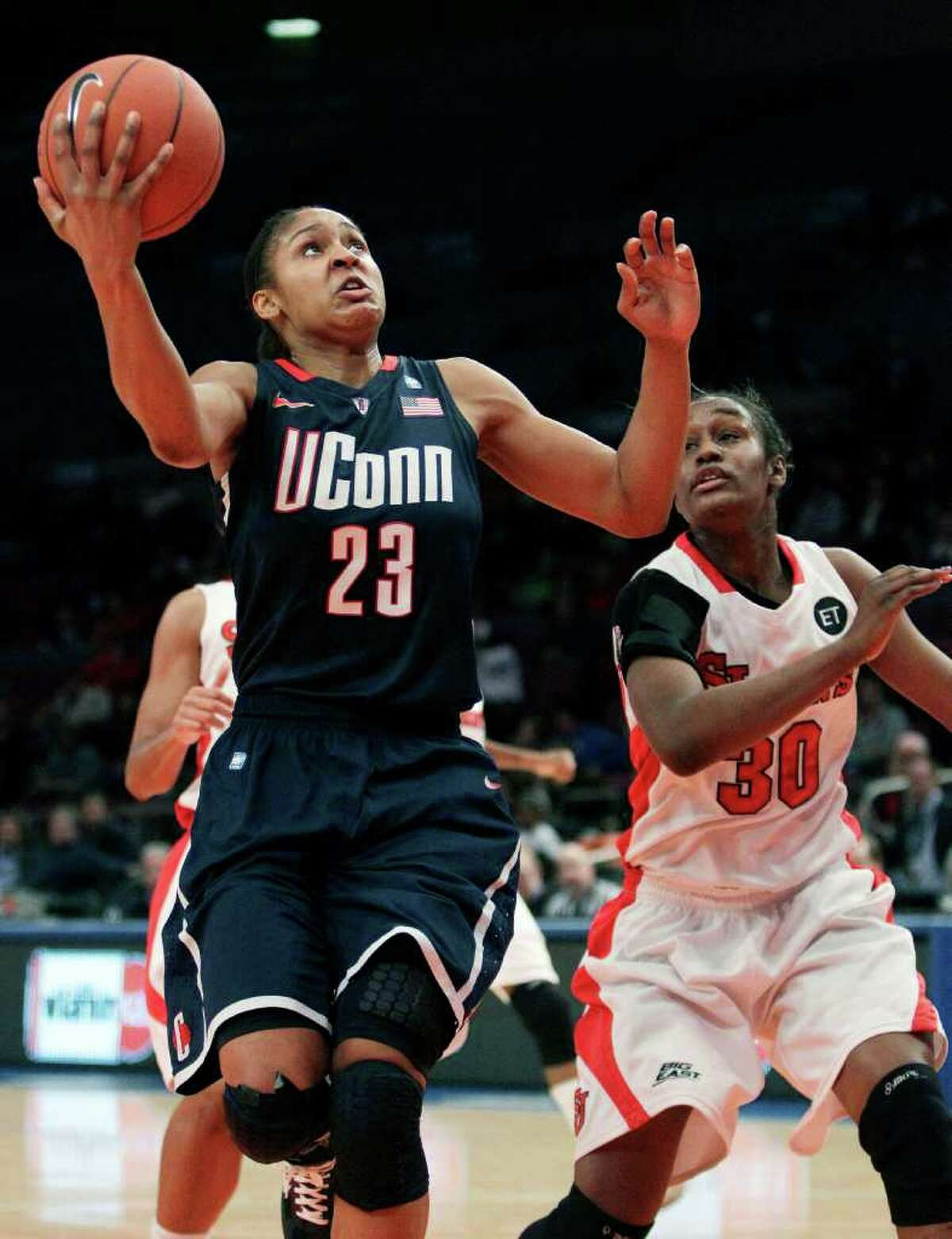 Connecticut's Maya Moore (23) drives past St. John's' Centhya Hart (30) during the first half of an NCAA college basketball game, Wednesday, Jan. 12, 2011, in New York. (AP Photo/Frank Franklin II)
