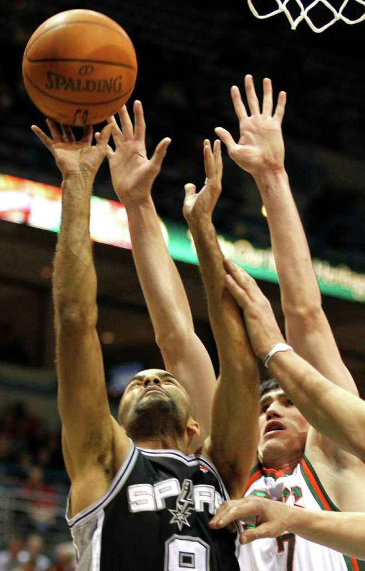 San Antonio Spurs' Tony Parker, left, puts up a shot against Milwaukee Bucks' Ersan Ilyasova in the first half of an NBA basketball game Wednesday, Jan. 12, 2011, in Milwaukee.