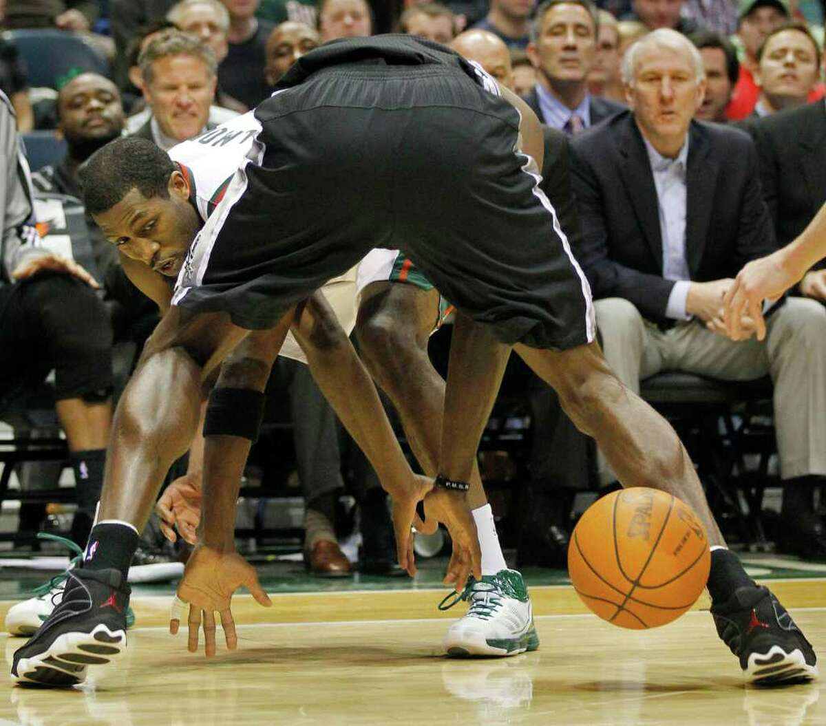 Milwaukee Bucks' John Salmons, left, reaches for a loose ball between the legs of San Antonio Spurs' Antonio McDyess in the second half of an NBA basketball game Wednesday, Jan. 12, 2011, in Milwaukee. San Antonio won 91-84.