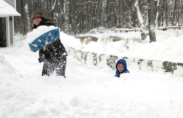 Under the watchful eye of her 8 year-old son Dante, Rosemary Field clears her driveway on Pansy Road in Fairfield, Conn. on Wednesday Jan. 12, 2011. Photo: Cathy Zuraw / Connecticut Post