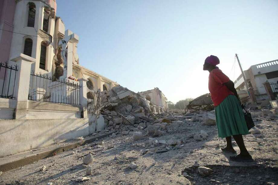 PORT-AU-PRINCE, HAITI - JANUARY 17:  A women says prayers in front of a Jesus statue next to the destroyed main Cathedral before an outdoor morning prayer service after the massive earthquake destroyed the building January 17, 2010 in Port-au-Prince, Haiti. Planeloads of rescuers and relief supplies headed to Haiti as governments and aid agencies launched a massive relief operation after a powerful earthquake that may have killed thousands. Many buildings were reduced to rubble by the 7.0-strong quake on January 12.  (Photo by Joe Raedle/Getty Images) Photo: Joe Raedle, Getty Images / 2010 Getty Images