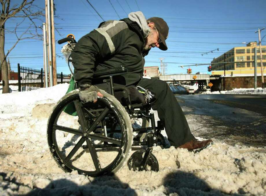 Disabled veteran Jules Saymon of Bridgeport pushes his wheelchair through the snow on the way to his bus stop on East Main Street in Bridgeport on Thursday, January 13, 2011. Photo: Brian A. Pounds / Connecticut Post