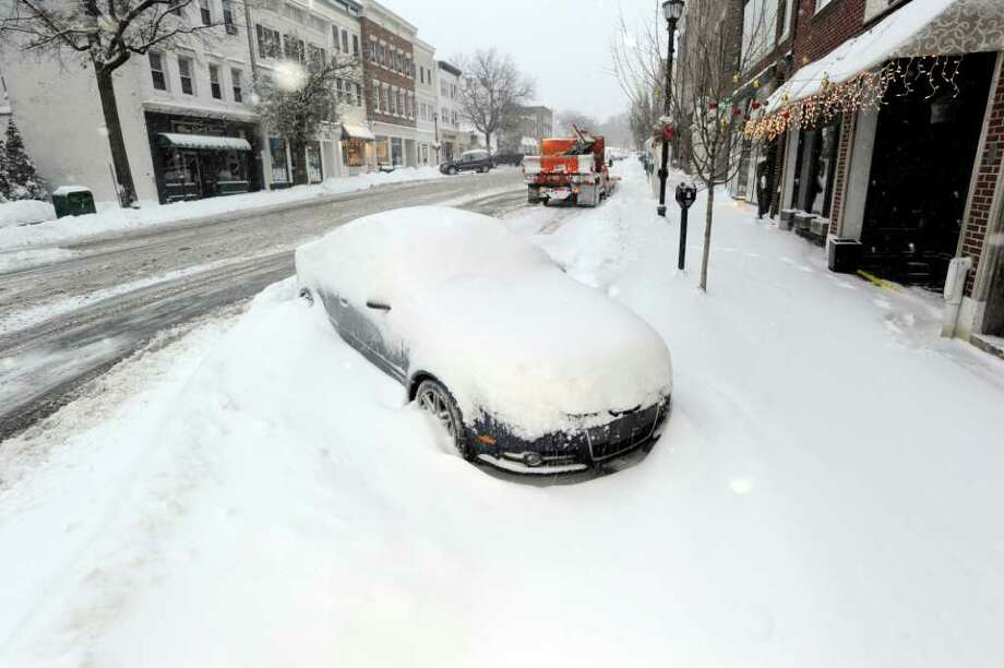 A snow-covered car parked at the bottom of Greenwich Avenue, Wednesday morning, Jan. 12, 2011. Photo: Bob Luckey, ST / Greenwich Time