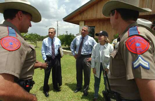 FOR METRO DAILY - U.S. Representative Charles Gonzalez (from left), U.S. Representative Henry Bonilla, and U.S. Senator Kay Bailey Hutchison talk with DPS troopers about the 2002 flood Friday July 12, 2002 at Canyon Lake during a tour of the damaged area.  PHOTO BY EDWARD A. ORNELAS/STAFF Photo: EDWARD A. ORNELAS, SAN ANTONIO EXPRESS-NEWS / SAN ANTONIO EXPRESS-NEWS