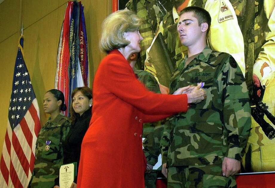 METRO: United States Senator Kay Bailey Hutchison pins the Purple Heart medal on Pfc. David Antonich during a ceremony Wednesday at Brooke Army Medical Center in which he and two other soldiers were awarded the medal for injuries sutained while serving in Iraq. The other recipients were Spc. Natasha Espinoza (far left) and Spc. Stanley M. Kremzar (behind Hutchison). Next to Espinoza is her mother Oralia Espinoza. JOHN DAVENPORT / STAFF Photo: JOHN DAVENPORT, SAN ANTONIO EXPRESS-NEWS / SAN ANTONIO EXPRESS-NEWS
